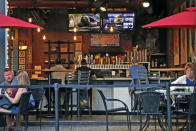 """FILE - In this Sunday, June 28, 2020 file photo, people gather at a bar in Pittsburgh. In July 2020, authorities are closing drinking establishments in some parts of the U.S. to stem the surge of COVID-19 infections — a move backed by sound science about risk factors that go beyond wearing or not wearing masks. In the words of one study, it comes down to the danger of """"heavy breathing in close proximity."""" (AP Photo/Gene J. Puskar)"""