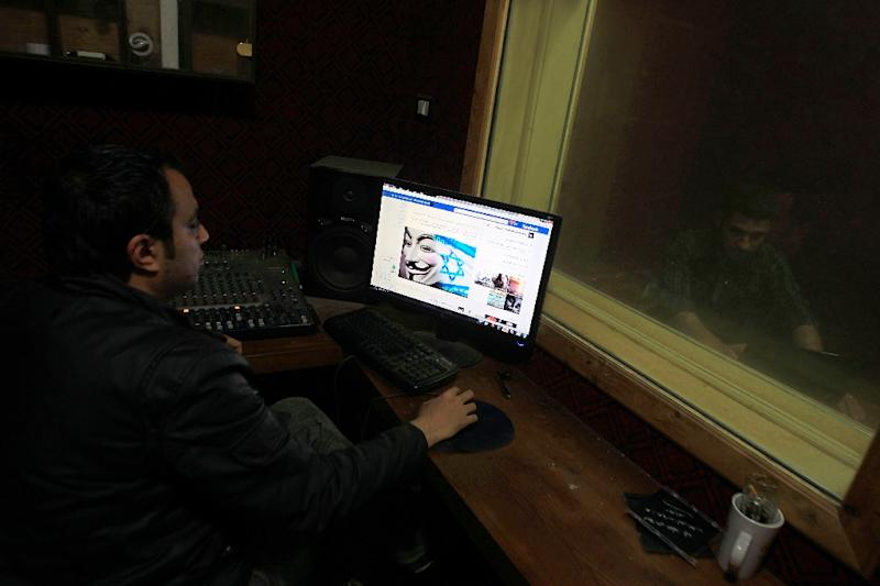 "A Palestinian man looks at Facebook page with a picture depicting the ""#Op_Israel"" campaign launched by the activist group Anonymous, in Gaza City on April 7, 2013"