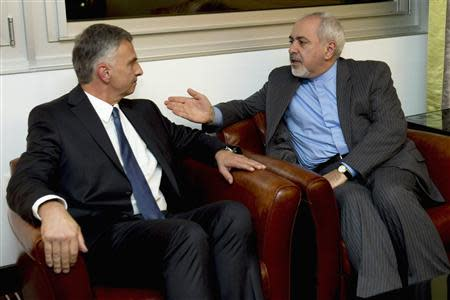 Switzerland's Foreign Minister Didier Burkhalter (L) speaks with his Iranian counterpart Mohammad Javad Zarif during a meeting ahead of talks on Iran's nuclear programme, in Geneva November 23, 2013. REUTERS/Keystone/Martial Trezzini/Pool