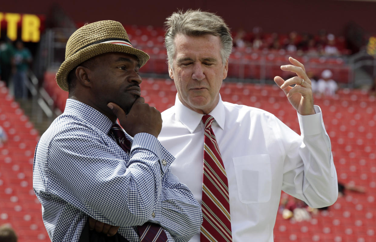 DeMaurice Smith, left, executive director of the National Football League Players' Association talks with Bruce Allen, Washington Redskins president, before an NFL football game against the Miami Dolphins,  Sunday, Sept. 13, 2015, in Landover, Md. (AP Photo/Mark Tenally)