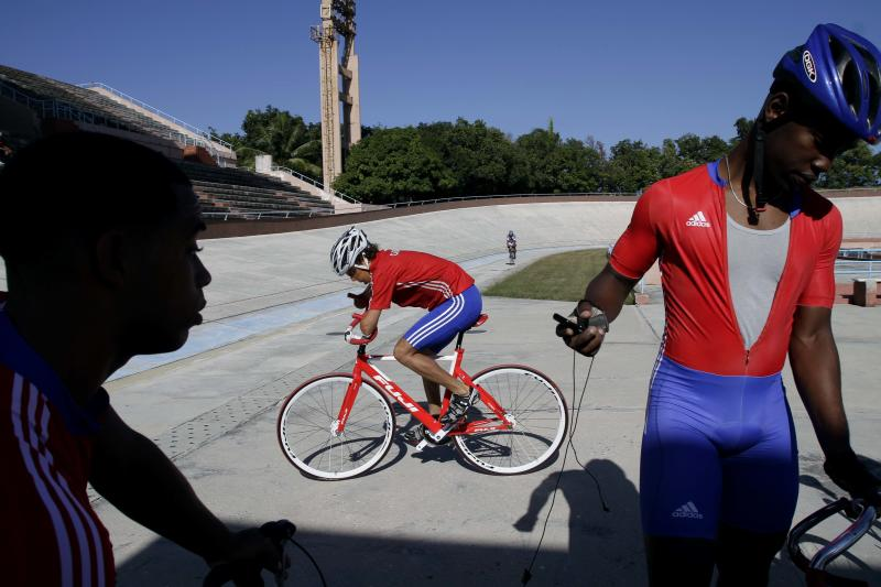 In this Jan. 26, 2012 photo, Damian Lopez, center, who was injured as a teenager by a high-voltage electrical wire when untangling a kite, prepares to train at the Reinaldo Paseiro velodrome in Havana, Cuba.  The accident cost him both his forearms, melted much of the skin from his face and left him in a coma from which doctors predicted he would never emerge. Twenty-two years later, Lopez, 35, is close to realizing an unlikely dream by representing Cuba at the 2012 London Paralympics in cycling, the sport that he says kept him from drowning in self-pity and despair.  (AP Photo/Franklin Reyes)