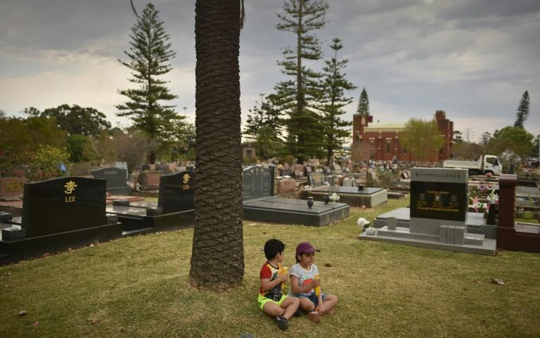 Young visitors sit amongst the gravestones to commemorate the 150-year anniversary of Rockwood -- the largest cemetery in the southern hemisphere -- in Sydney