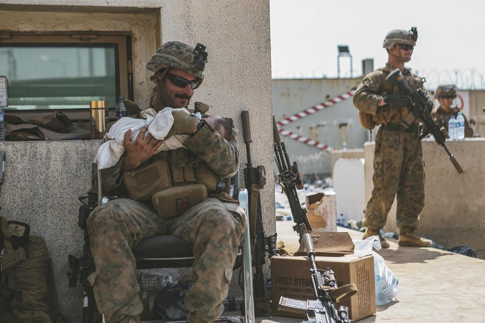 In this image provide by the U.S. Marine Corps, a Marine assigned to the 24th Marine Expeditionary Unit (MEU) calms an infant during an evacuation at Hamid Karzai International Airport, in Kabul, Afghanistan, Friday, Aug. 20, 2021. (Sgt. Isaiah Campbell/U.S. Marine Corps via AP)