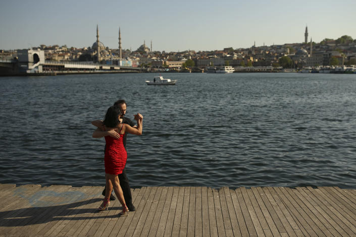 A couple dance by the Golden Horn leading to the Bosphorus Strait separating Europe and Asia, in Istanbul, Friday, May 14, 2021. Turkey is in the final days of a full coronavirus lockdown and the government has ordered people to stay home and businesses to close amid a huge surge in new daily infections. But millions of workers are exempt and so are foreign tourists. Turkey is courting international tourists during an economic downturn and needs the foreign currencies that tourism brings to help the economy as the Turkish lira continues to sink. (AP Photo/Emrah Gurel)