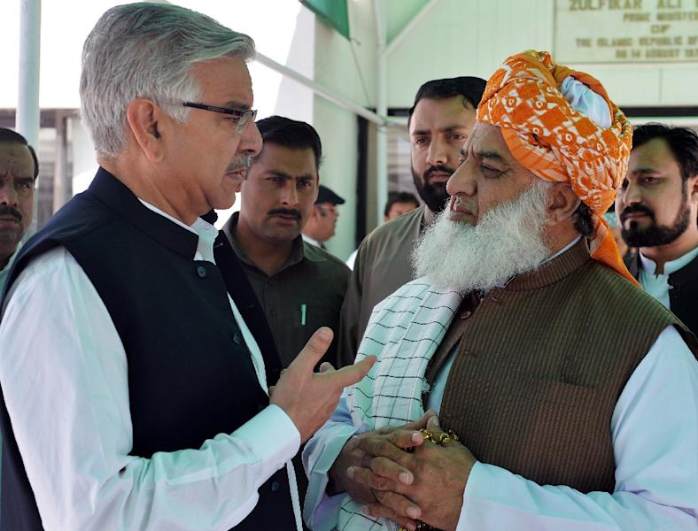 Pakistan's Defence Minister Khawaja Asif (L) and the chief of hardline religious party Jamiat Ulema Islam (JUI) Maulana Fazalur Rehman talk as they leave Parliament House in Islamabad on April 10, 2015 (AFP Photo/Aamir Qureshi)