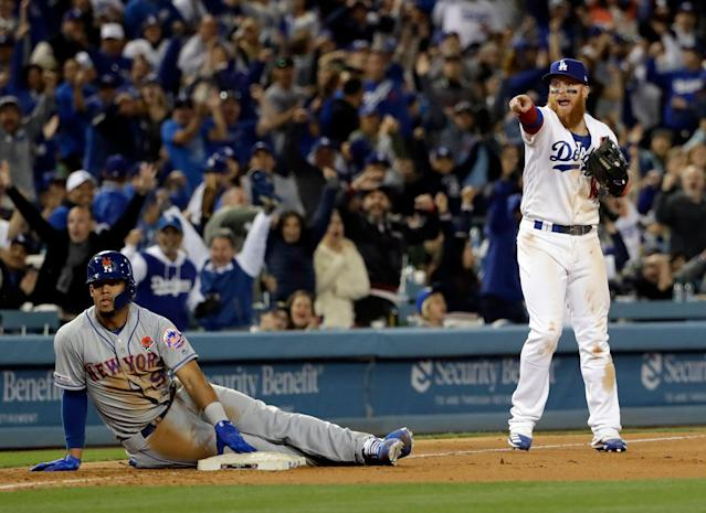 Los Angeles Dodgers third baseman Justin Turner, right, points to home plate after tagging out New York Mets' Carlos Gomez at third base on a fly ball to right field from J.D. Davis during the eighth inning of a baseball game, Monday, May 27, 2019, in Los Angeles. (AP Photo/Marcio Jose Sanchez)