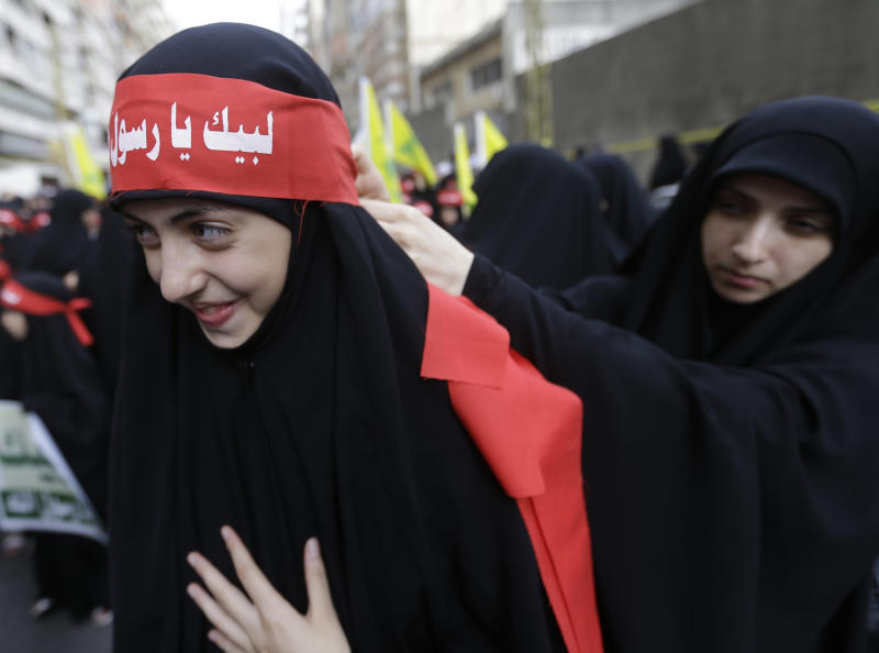 "A veiled Hezbollah supporters ties a banner on her friend's forehead, that reads in Arabic, ""At your service God's prophet,"" during a rally denouncing an anti-Islam film that has provoked a week of unrest in Muslim countries worldwide, in the southern suburb of Beirut, Lebanon, Monday Sept. 17, 2012. Hezbollah's leader Hassan Nasrallah, not shown, who does not usually appear in public for fear of assassination, called for Monday's protests in Beirut, saying the U.S. must be held accountable for the film because it was produced in America. (AP Photo/Hussein Malla)"