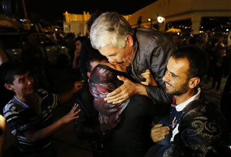 One of the nine newly released Lebanese hostages, who were held by rebels in northern Syria, kisses his wife upon his arrival at Beirut international airport, October 19, 2013. REUTERS/Mohamed Azakir