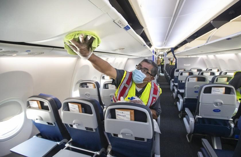 LOS ANGELES, CA -JULY 09, 2020: Cleaning supervisor Jose Mendoza disinfects the cabin area of a United Airlines 737 jet before passengers are allowed to board at LAX on Thursday, July 9, 2020 in Los Angeles, CA. (Mel Melcon / Los Angeles Times)