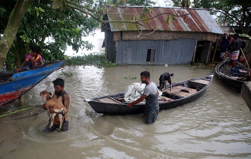 Photo shows people with boat struggling in floodwaters in a village at Louhajang upazila in Munshiganj, Bangladesh, on July 29, 2020. Source: Getty