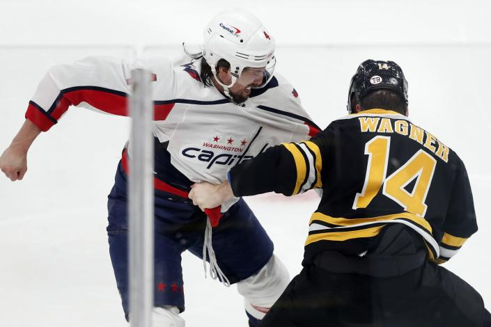 Washington Capitals' Brenden Dillon and Boston Bruins' Chris Wagner (14) fight during the first period of an NHL hockey game, Sunday, April 11, 2021, in Boston. (AP Photo/Michael Dwyer)