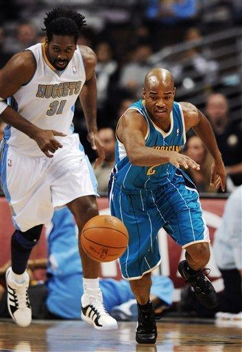 New Orleans Hornets guard Jarrett Jack, right, runs after a loose ball as Denver Nuggets forward Nene, of Brazil, pursues during the first quarter of an NBA basketball game on Monday, Jan. 9, 2012, in Denver. (AP Photo/Chris Schneider)