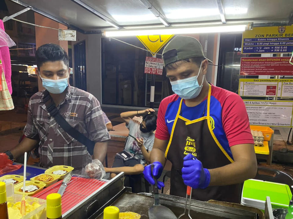 Burger stall proprietor Ahmad Lokman, 35, (right) said he will drive back with his wife to his hometown in Batu Pahat on Thursday evening. — Picture by Ben Tan