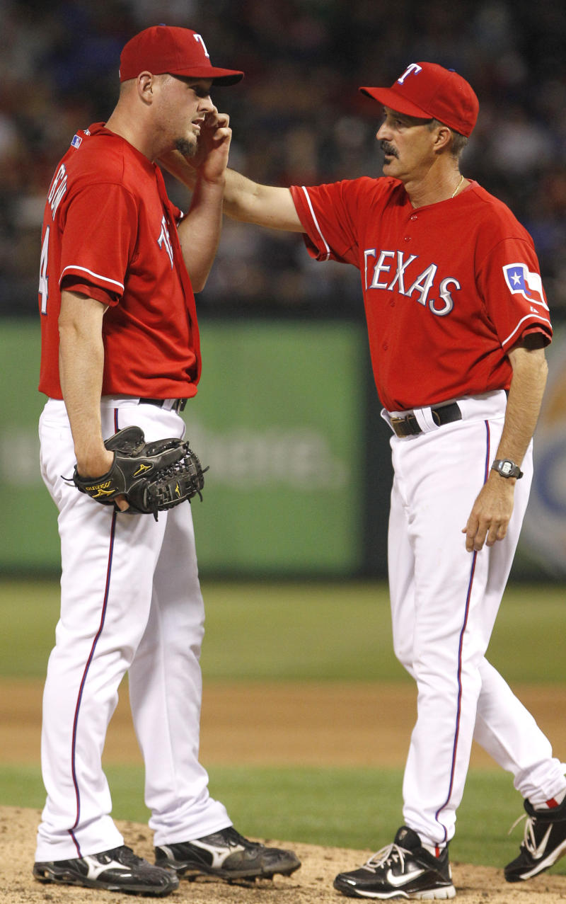 Texas Rangers starting pitcher Matt Harrison, left, gets a visit at the mound from pitching coach Mike Maddux during the sixth inning of a baseball game against the New York Yankees in Arlington, Texas, Friday, May 6, 2011. The Yankees won 4-1.  (AP Photo/LM Otero)