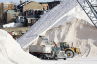 Road salt is poured into a truck, Wednesday, Dec. 16, 2020, at Eastern Salt Company in Chelsea, Mass., as preparation continues for a storm that is expected to dump a foot or more of snow throughout the Northeast. (AP Photo/Elise Amendola)