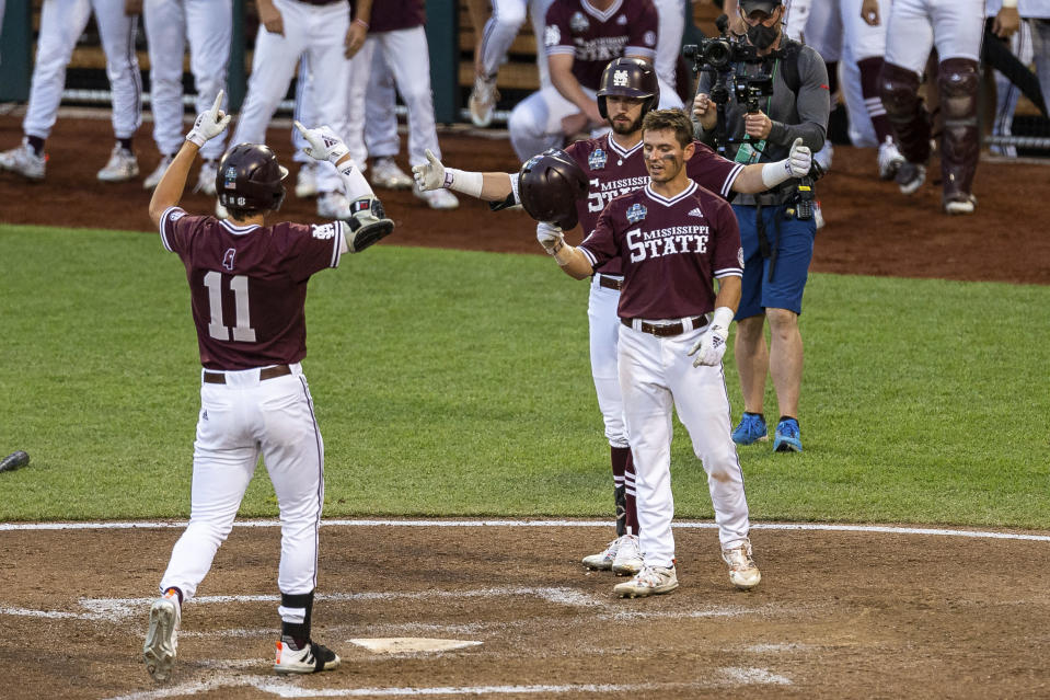 Mississippi State infielder Kellum Clark (11) celebrates his two run homer with Scott Dubrule in the eighth inning against Virginia during a baseball game in the College World Series Tuesday, June 22, 2021, at TD Ameritrade Park in Omaha, Neb. (AP Photo/John Peterson)