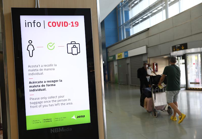 A Covid-19 information sign telling passengers to respect social distancing measures while checking their luggages at Ibiza international airport, Spain, where the tourism industry has been hit hard by the latest 14-day quarantine requirement by the British government for all tourists that travel from Spain because of its high levels of COVID-19 cases. Picture date: Saturday August 1, 2020.