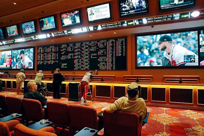 People make bets at the South Point hotel and casino sports book in Las Vegas, as an Atlanta Braves game plays.