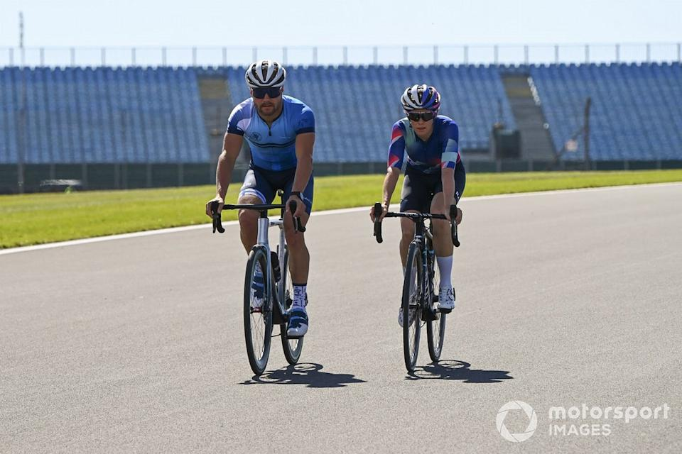 """Valtteri Bottas, Mercedes-AMG F1 and Tiffany Cromwell cycle the track<span class=""""copyright"""">Mark Sutton / Motorsport Images</span>"""