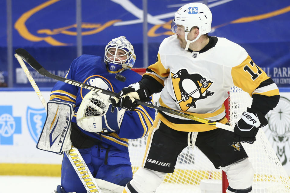 Buffalo Sabres goalie Dustin Tokarski (31) stops a tipped shot by Pittsburgh Penguins forward Bryan Rust (17) during the second period of an NHL hockey game, Sunday, April 18, 2021, in Buffalo, N.Y. (AP Photo/Jeffrey T. Barnes)