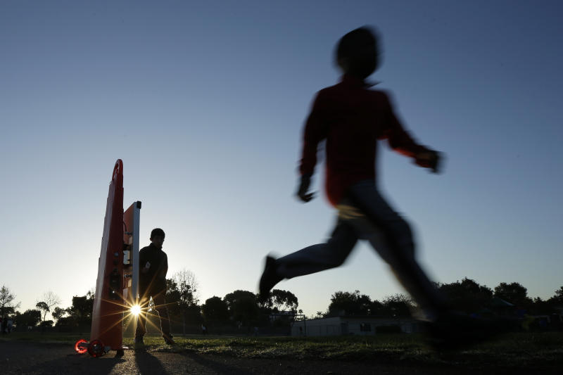 In this March 14, 2014 picture, students take part in an early morning running program at an elementary school in Chula Vista, Calif. Amid alarming national statistics showing an epidemic in childhood obesity, hundreds of thousands of students across the country are being weighed and measured. The Chula Vista Elementary School District is being touted as a model for its methods that have resulted in motivating the community to take action. (AP Photo/Gregory Bull)