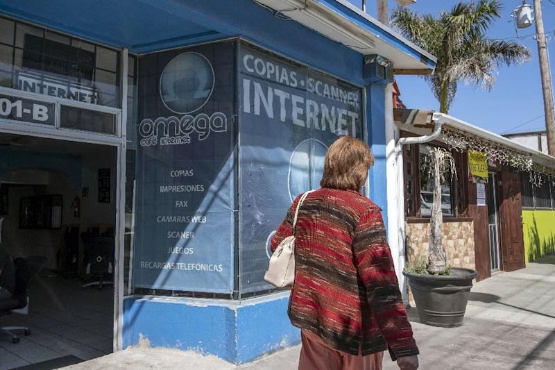 A woman walks past Omega Internet Cafe in Rosarito, Mexico, where Thomas Markle admitted he set up staged paparazzi photos (AFP Photo/GUILLERMO ARIAS)