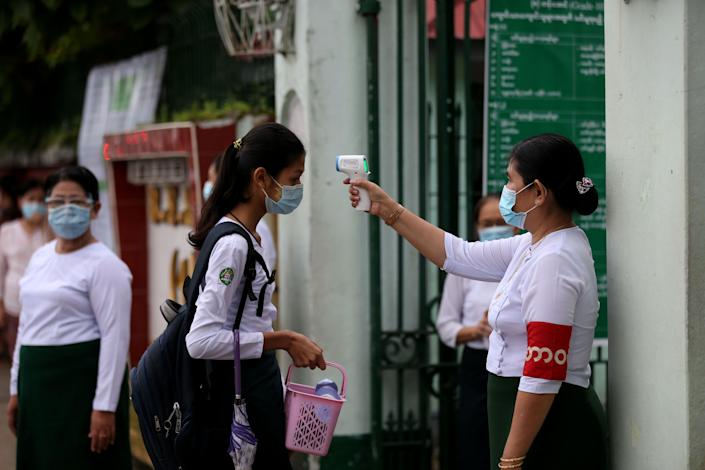 A teacher wearing a face mask measures a student's body temperature at the entrance to a reopened high school in Yangon, Myanmar, on July 21. Myanmar reopened over half of its high schools since coronavirus suspensions.
