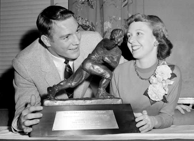 "In this Dec. 8, 1955, file photo, All-America Howard ""Hopalong"" Cassady, halfback for Ohio State, and his wife, Barbara, pose with the Heisman Trophy awarded to Cassady in New York. Cassady, a Heisman Trophy winner and former NFL running back, died early Friday, Sept. 20, 2019, in Tampa, Fla., Jerry Emig, the Ohio State associate athletic director said. He was 85. Cassady played both football and baseball at Ohio State in the early 1950s, winning the Heisman Trophy in 1955. He also played 10 seasons in the NFL, mostly with the Detroit, and got the nickname ""Hopalong"" from local sports writers after the black-hatted Western star of the 1950s. (AP Photo)"