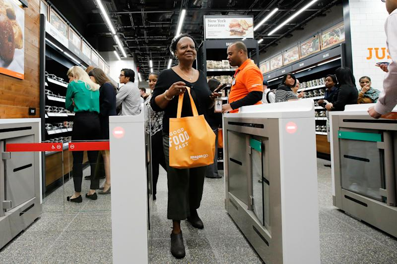 A customer carries her shopping bag as she walks out of a newly-opened Amazon Go store, Tuesday, May 7, 2019 in New York. The store will be the first Amazon Go store to accept cash. At its other shops, customers can only enter with an app that links to a credit card or an Amazon account.(AP Photo/Mark Lennihan)