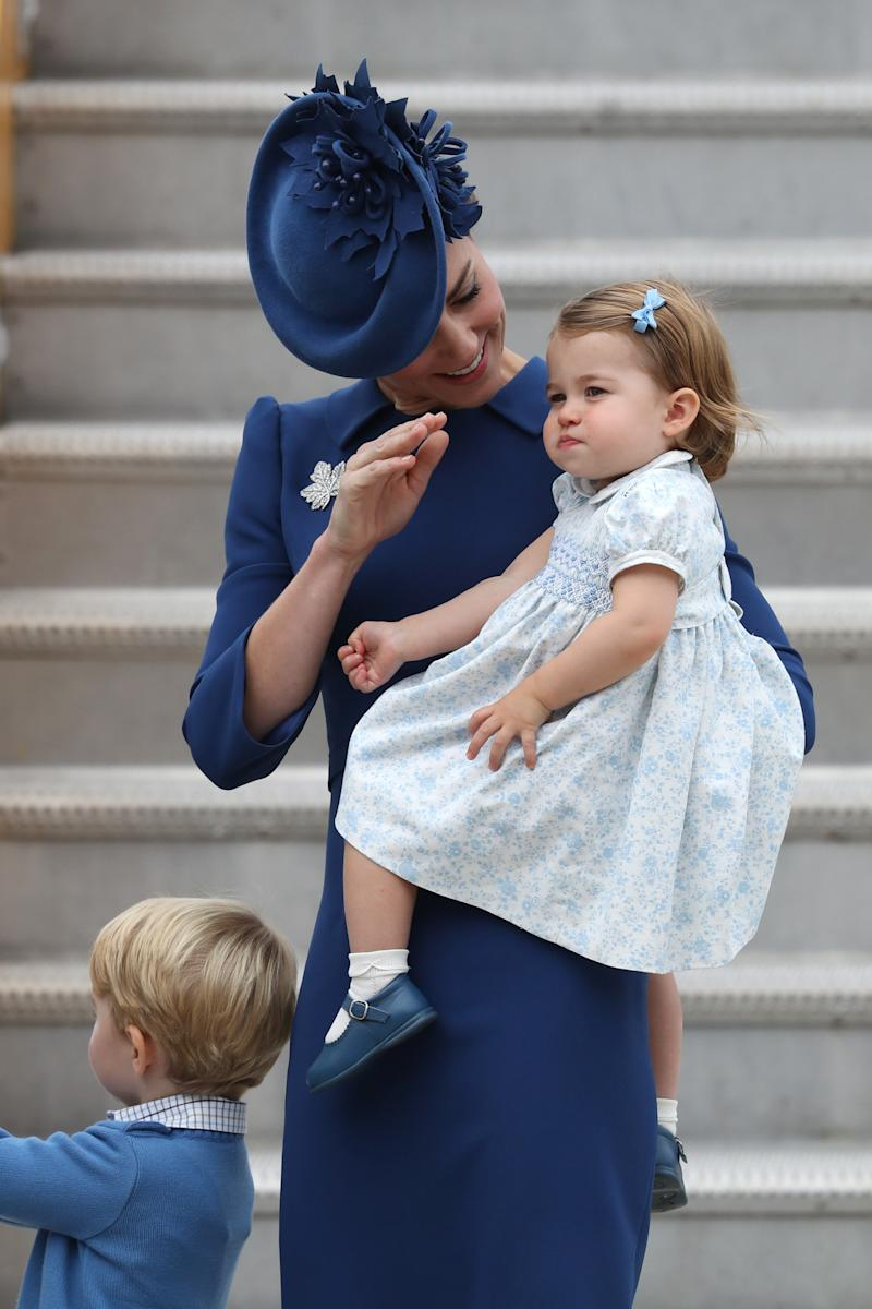 In Canada on her first Royal Tour last fall, Princess Charlotte received her first lessons in the royal wave, while dressed in a blue printed dress, white ankle socks, and blue mary-jane shoes.