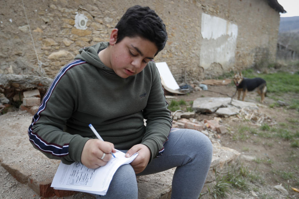 Mihaly Kovacs, a 12 year-old Hungarian boy, works on his homework outside his home in Bodvaszilas, Hungary, Monday, April 12,2021. Many students from Hungary's Roma minority do not have access to computers or the internet and are struggling to keep up with online education during the pandemic. Surveys show that less than half of Roma families in Hungary have cable and mobile internet and 13% have no internet at all. (AP Photo/Laszlo Balogh)