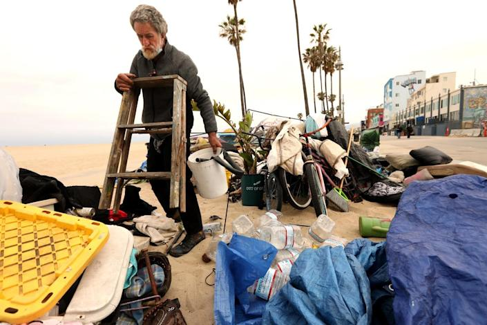 A man gathers belongings from a camp