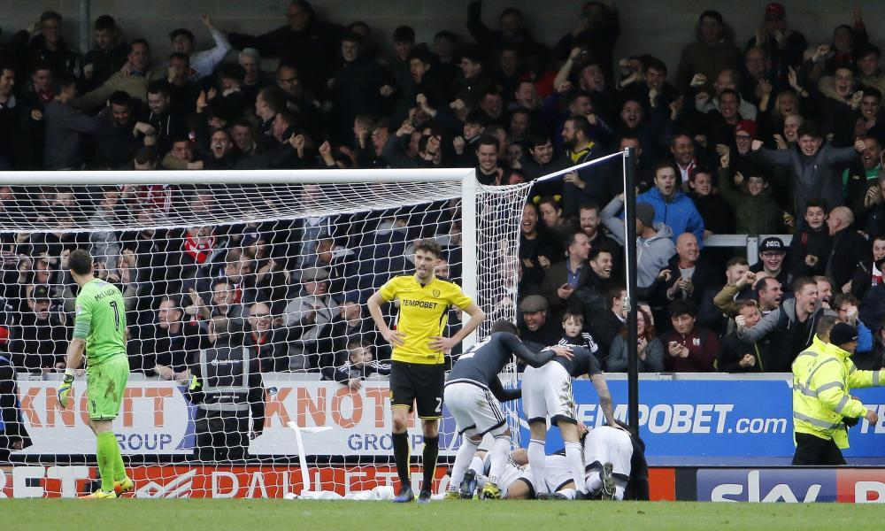Brentford players and fans celebrate after Lasse Vibe's winner at Burton Albion.