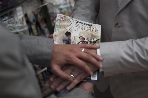 Jason Welker (L) and Scott Everhart pose with their bands on top of an X-Men comic book after exchanging wedding vows at a comic book retail shop in Manhattan, New York June 20, 2012.