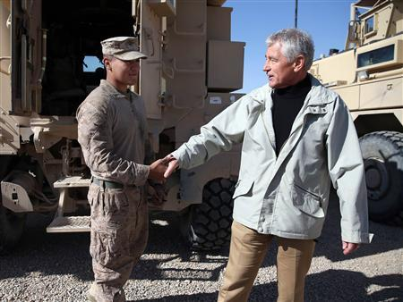 U.S. Secretary of Defense Chuck Hagel speaks with U.S. Marine Lance Corporal Arron Corona as he works on a MRAP vehicle during a visit to Camp Bastion