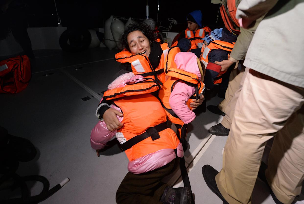 Syrians woman holds her children after 50 refugees captured by Turkish coast guard while they were illegally trying to reach Greece's Kastellorizo island, in shores of Kas District of Antalya, southern province of Turkey on February 24, 2016.