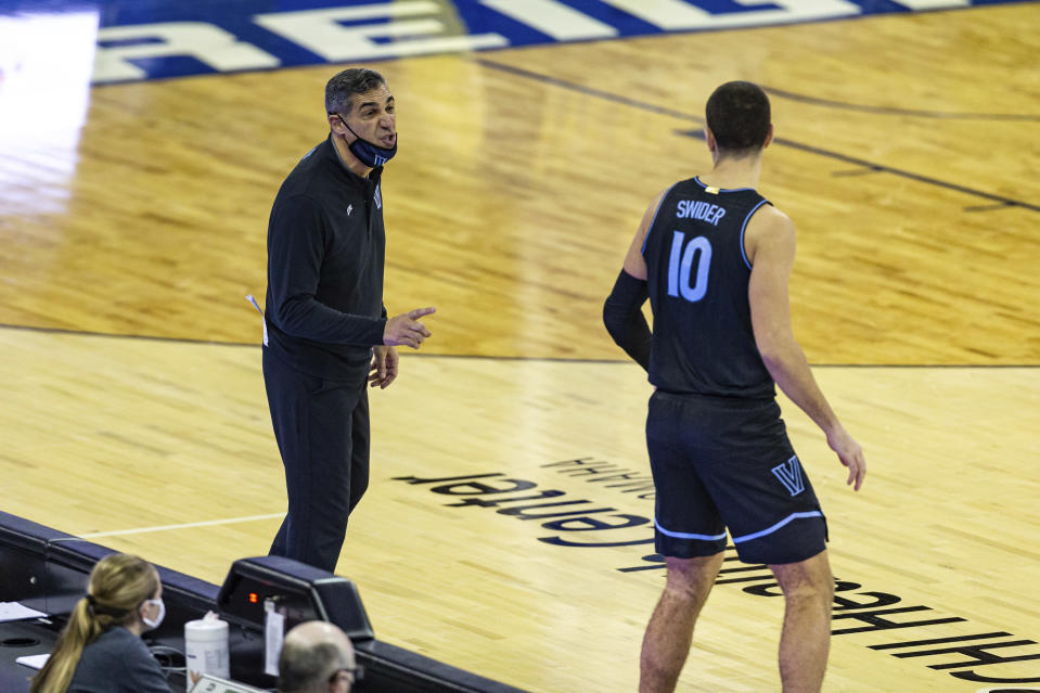 Villanova head coach Jay Wright, left, gives forward Cole Swider (10) instructions before Swider goes in to play against Creighton in the second half during an NCAA college basketball game Saturday, Feb. 13, 2021, in Omaha, Neb. (AP Photo/John Peterson)