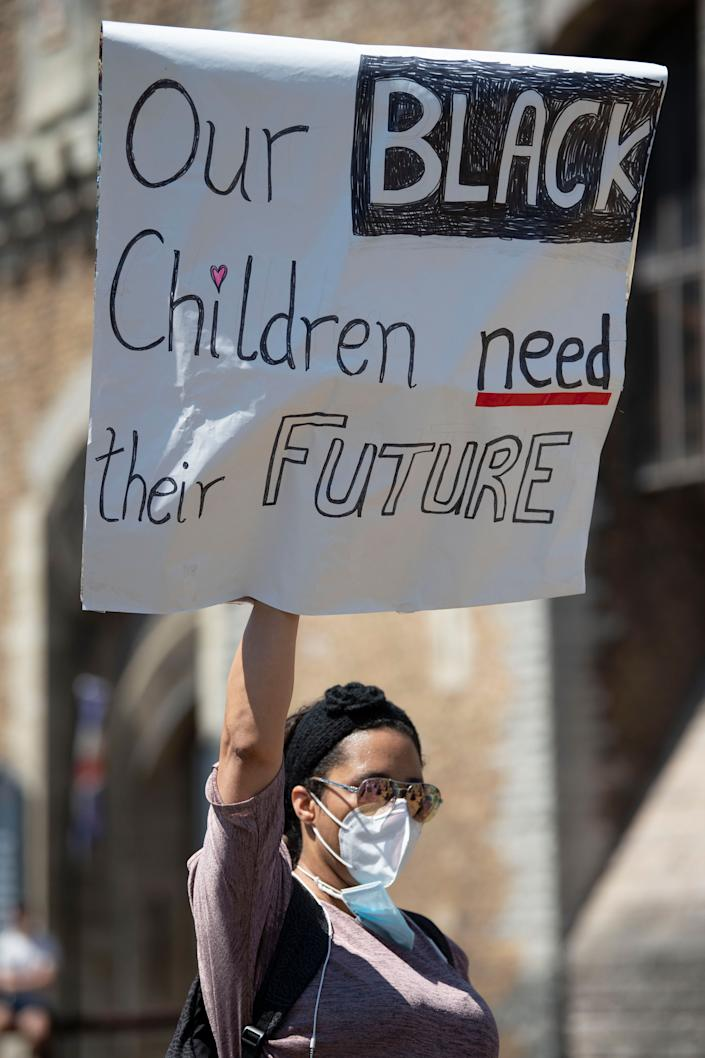 """<i>A woman holds up a sign that says """"Our black children need a future"""" during a May 31 protest outside Cardiff Castle in Wales/</i>"""