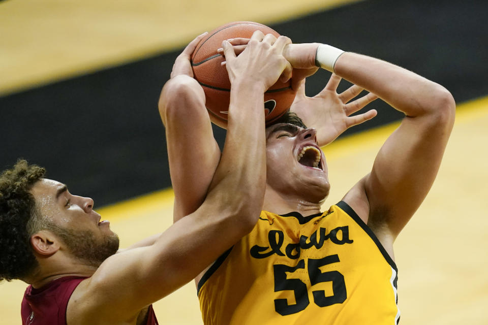 Indiana forward Race Thompson fights for a rebound with Iowa center Luka Garza (55) during the second half of an NCAA college basketball game, Thursday, Jan. 21, 2021, in Iowa City, Iowa. Indiana won 81-69. (AP Photo/Charlie Neibergall)