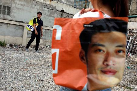 Fashion designer Panupong Chansopa poses for a photo with his tote bags made from old election campaign posters near his home in Bangkok, Thailand April 8, 2019. REUTERS/Soe Zeya Tun