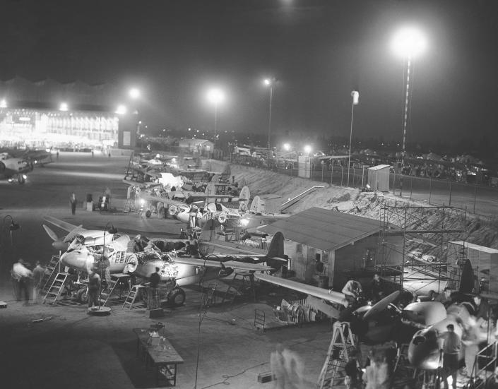 FILE - In this July 12, 1941, file photo, the final assembly of Lockheed P-38 pursuit planes at the Burbank, Calif., plant takes place outdoors under powerful floodlights, because of lack of room inside the plant. Not since World War II, when people carried Ration Books, when buying cars, firewood and nylon was restricted, when men were drafted and women volunteered in the war effort, has the entire nation been asked to truly sacrifice for a greater good. (AP Photo, File)