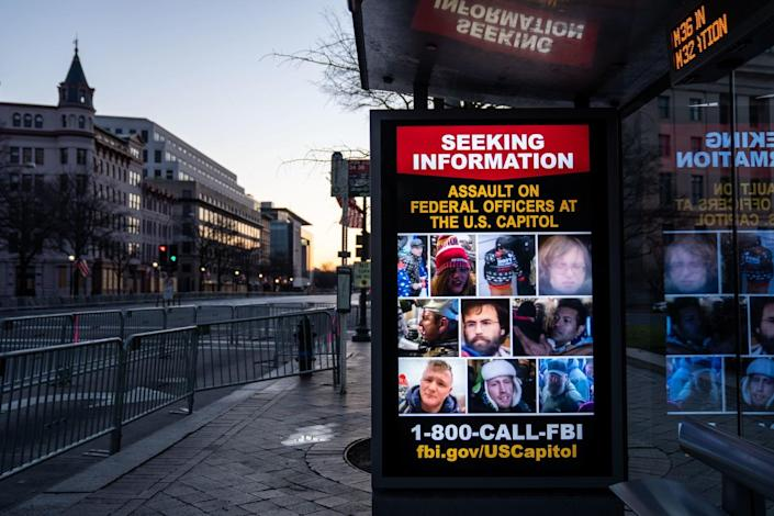 Signs at bus stations ask for information about people who breached the U.S. Capitol on Jan. 6.