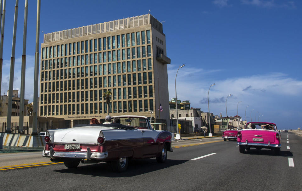 """FILE - In this Oct. 3, 2017, file photo, tourists ride classic convertible cars on the Malecon beside the United States Embassy in Havana, Cuba. The Biden administration faces increasing pressure to respond to a sharply growing number of reported injuries suffered by diplomats, intelligence officers and military personnel that some suspect are caused by devices that emit waves of energy that disrupt brain function. The problem has been labeled the """"Havana Syndrome,"""" because the first cases affected personnel in 2016 at the U.S. Embassy in Cuba. (AP Photo/Desmond Boylan, File)"""