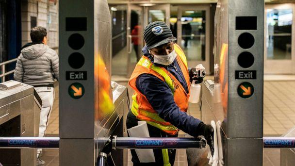 PHOTO: An MTA transit worker cleans a nearly empty Times Square - 42nd street subway station following the outbreak of the coronavirus, in New York City, March 16, 2020. (Jeenah Moon/Reuters)