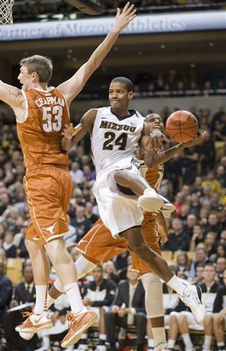 Missouri's Kim English, center, passes the all under the basket around Texas' Clint Chapman, left, and Texas' Jonathan Holmes, right, during the second half of an NCAA college basketball game Saturday, Jan. 14, 2012, in Columbia, Mo. Missouri won the game 84-73. (AP Photo/L.G. Patterson)