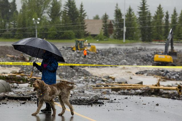 CANMORE, CANADA- JUNE 21: A woman walks along the edge of Eagle Terrace Road which collapsed into the river, looks at the destruction along the Cougar Creek June 21, 2013 in Canmore, Alberta, Canada. Widespread flooding caused by torrential rains washed out bridges and roads prompting the evacuation of thousnds. (Photo by John Gibson/Getty Images)