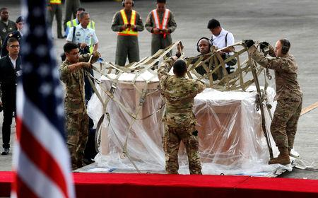 U.S Air Force personnel remove the cover of crates containing the bells of Balangiga after their arrival at Villamor Air Base in Pasay Metro Manila Philippines