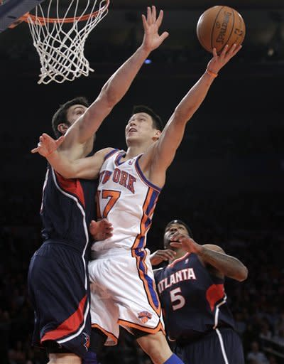 New York Knicks guard Jeremy Lin (17) goes up for a layup next to Atlanta Hawks center Zaza Pachulia (27) in the first quarter of an NBA basketball game at Madison Square Garden in New York, Wednesday, Feb. 22, 2012. Hawks forward Josh Smith is at right. (AP Photo/Kathy Willens)