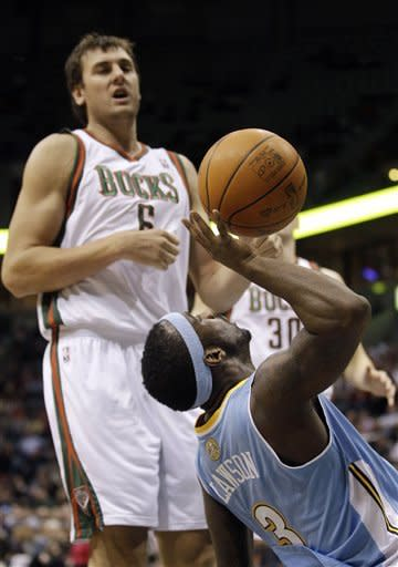 Denver Nuggets' Ty Lawson (3) shoots after a foul by Milwaukee Bucks' Andrew Bogut (6) during the first half of an NBA basketball game Tuesday, Jan. 17, 2012, in Milwaukee. (AP Photo/Morry Gash)