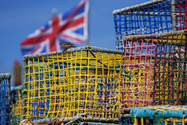 Empty fishing nets sit on the beach at Hastings, Sussex (Steve Parsons/PA)